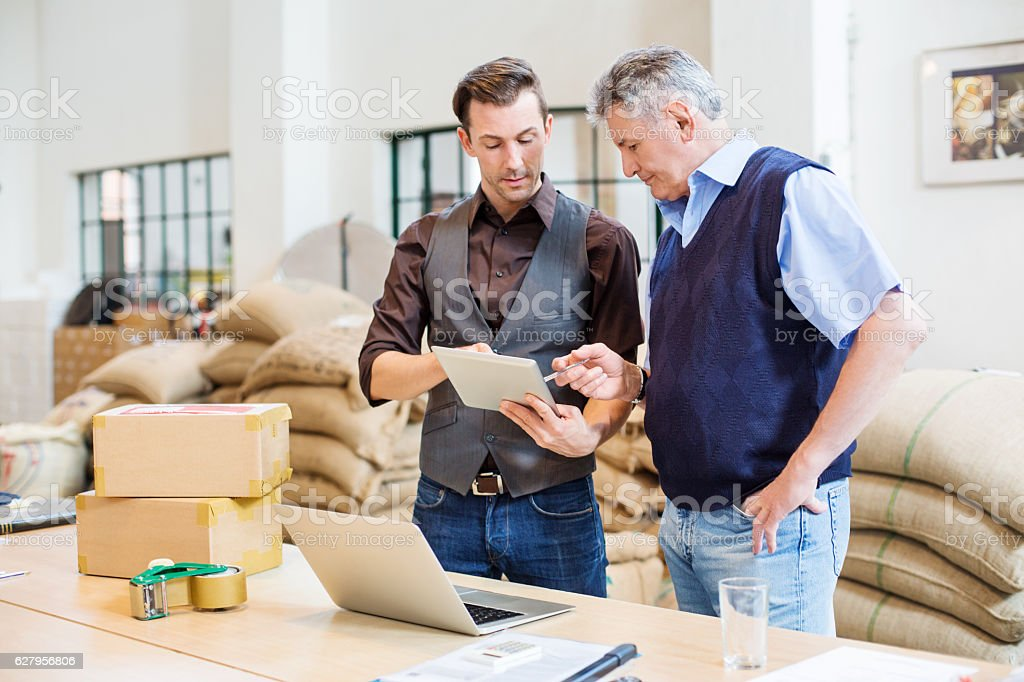 Two business men at coffee storage room stock photo