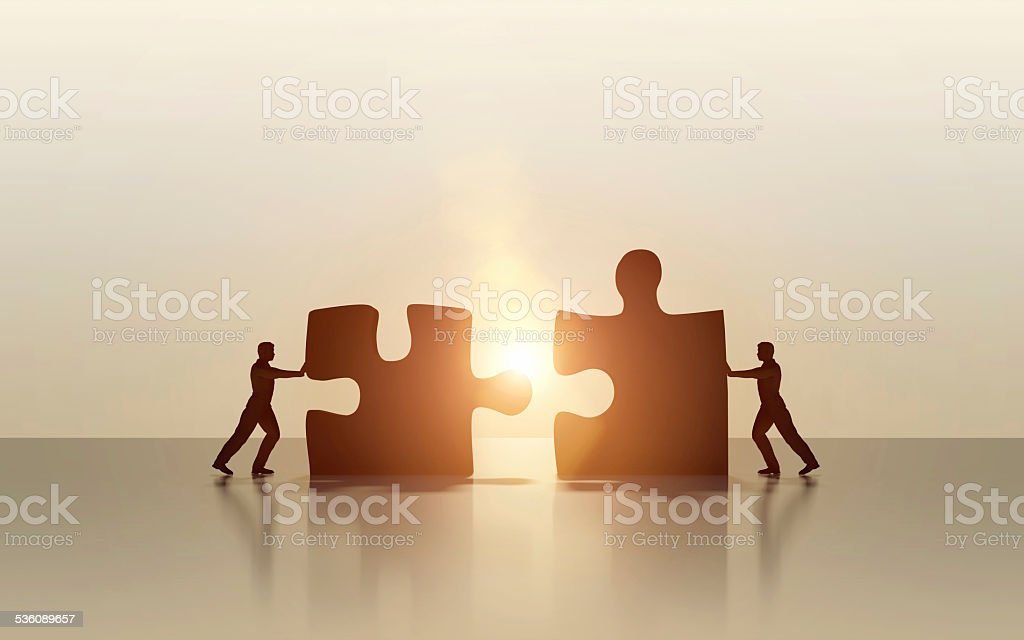 Two business men connecting and solving puzzle stock photo