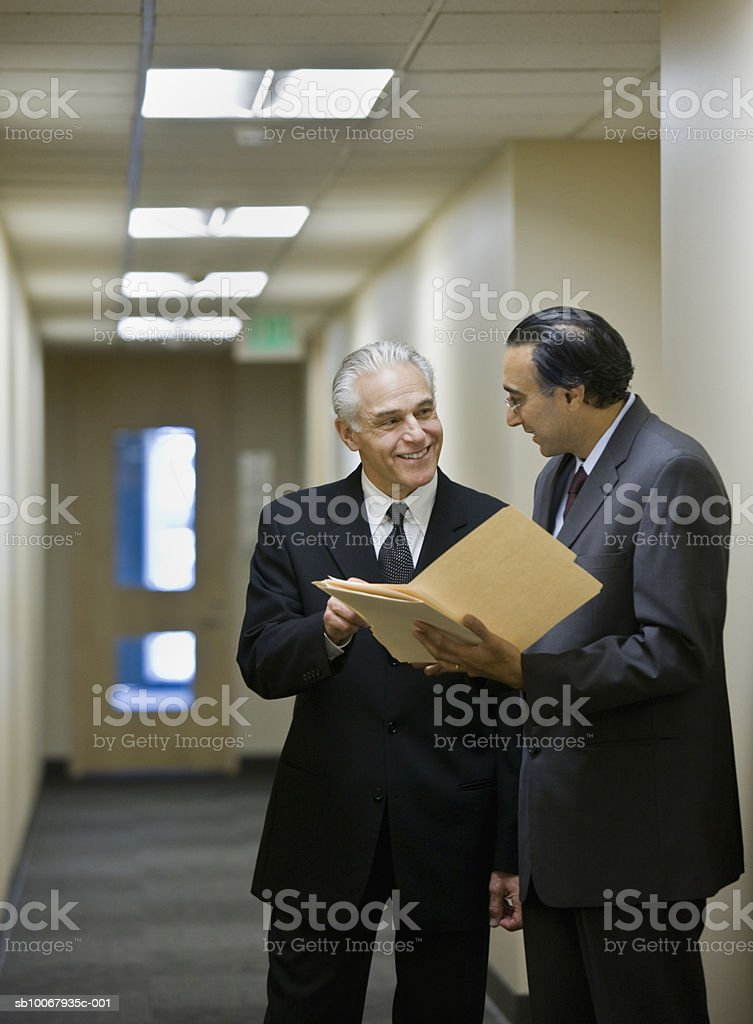 Two business men discussing documents in corridor royalty-free stock photo