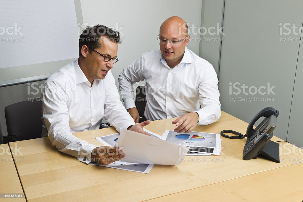 Two Business men in office discussing/reviewing reports royalty-free stock photo