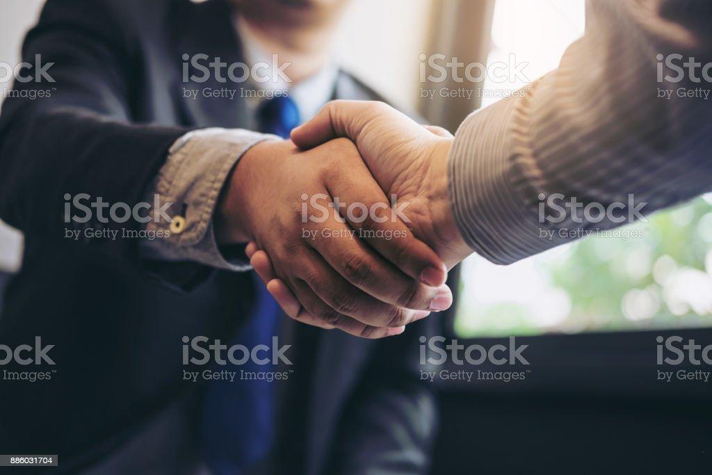 Dos empresarios estrecharme la mano durante una reunión para firmar el acuerdo y convertirse en un socio de negocios, empresas, empresas, seguros, éxito tratando, contratación entre sus empresas foto de stock libre de derechos