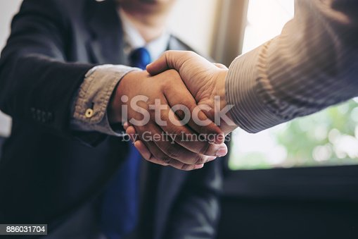 istock Two business men shaking hands during a meeting to sign agreement and become a business partner, enterprises, companies, confident, success dealing, contract between their firms. 886031704