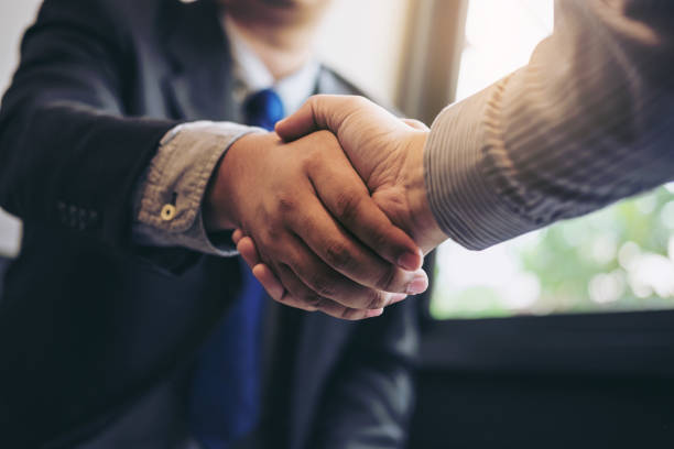 Two business men shaking hands during a meeting to sign agreement and become a business partner, enterprises, companies, confident, success dealing, contract between their firms - foto stock