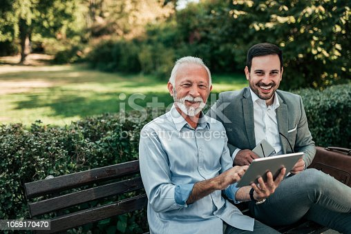 Two business men sitting in the park and using tablet.
