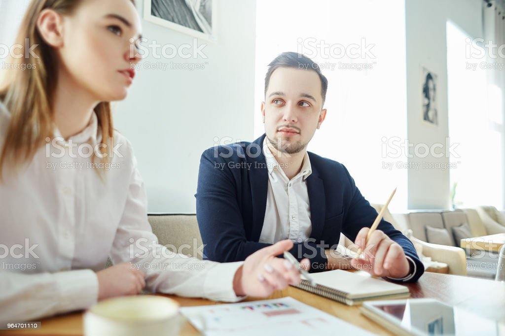 Two business partners discussing report with financial stats at meeting; businessman listening to his female colleague royalty-free stock photo