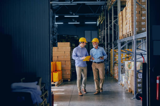 Two business partners in formal wear and with protective yellow helmets on heads walking and talking about business. Younger one holding folder with data while older one using tablet. Two business partners in formal wear and with protective yellow helmets on heads walking and talking about business. Younger one holding folder with data while older one using tablet. manufacturing stock pictures, royalty-free photos & images