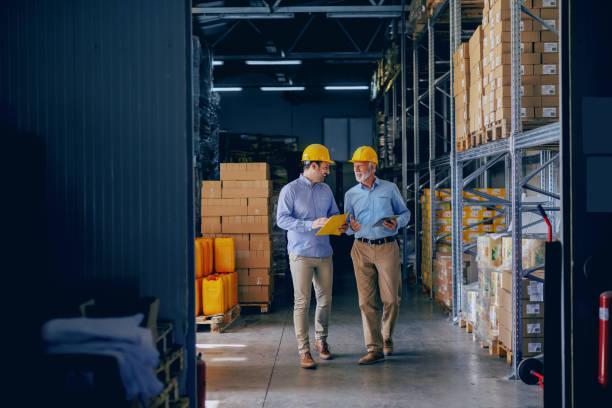 twee zakelijke partners in formele slijtage en met beschermende gele helmen op het hoofd lopen en praten over het bedrijfsleven. jongere één holdings omslag met gegevens terwijl oudere gebruikend tablet. - manufacturing stockfoto's en -beelden