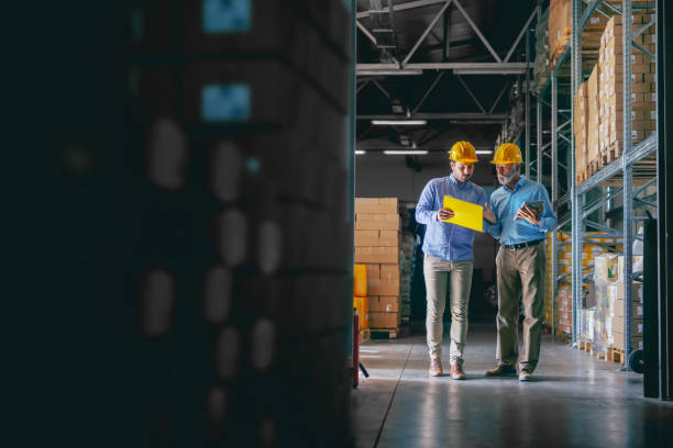 Two business partners in formal wear and with protective yellow helmets on heads standing in warehouse and comparing data. Younger one pointing at document in folder while older one holding tablet. Two business partners in formal wear and with protective yellow helmets on heads standing in warehouse and comparing data. Younger one pointing at document in folder while older one holding tablet. food warehouse stock pictures, royalty-free photos & images