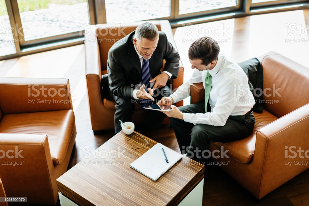 Two Business Partners Looking At Digital Tablet stock photo