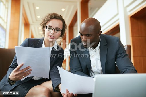 istock Two business partners sitting in cafe and discussing contract. 493552404