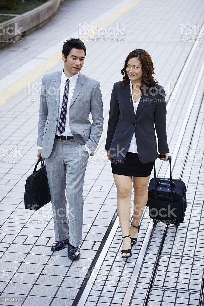 Two business partners with luggage walking on the street royalty-free stock photo