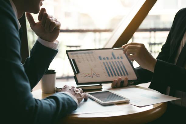 dos estrategias de análisis de compañeros de trabajo de asociación empresarial y gestuing con la discusión de un gráfico de planificación financiera y el presupuesto de la empresa durante una reunión de presupuesto en la sala de oficinas. - financial planning fotografías e imágenes de stock