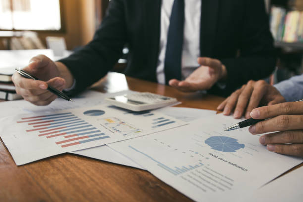 two business partnership coworkers analysis strategy with discussing a financial planning graph and company budget during a budget meeting in office room. - financial planning stock pictures, royalty-free photos & images