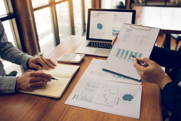 Zwei Mitarbeiter der Unternehmenspartnerschaft analysieren die Strategie mit der Erörterung eines Finanzplanungsdiagramms und des Unternehmensbudgets während einer Budgetsitzung im Büroraum. – Foto