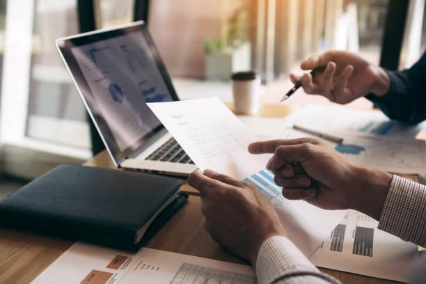 Zwei Mitarbeiter der Geschäftspartnerschaft und gestikulieren mit der Diskussion eines Finanzplanungsdiagramms und eines Unternehmens während einer Budgetsitzung im Büroraum. – Foto