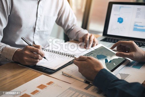 Two business partnership coworkers discussing a financial planning graph and company during a budget meeting in office room.