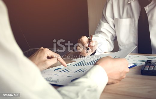 672116416istockphoto Two business people analysis summary report graph together. 859967592
