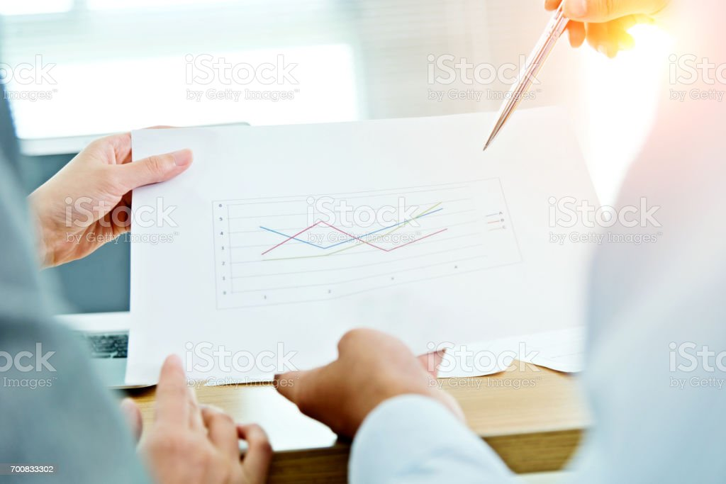 Two business people are analyzing the line graph stock photo