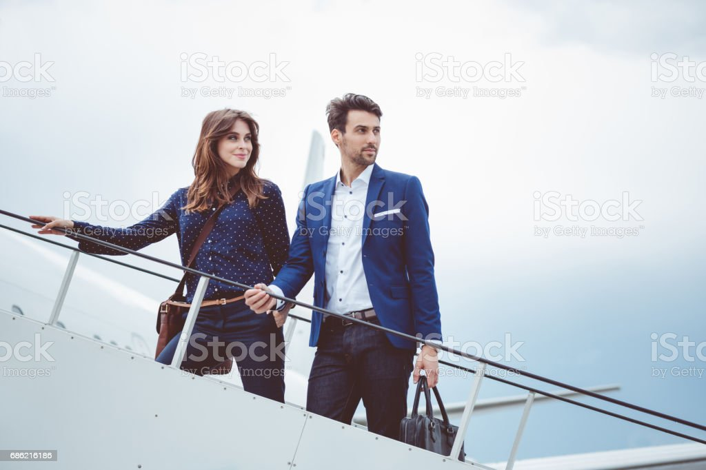 Two business people boarding airplane, going on business trip.