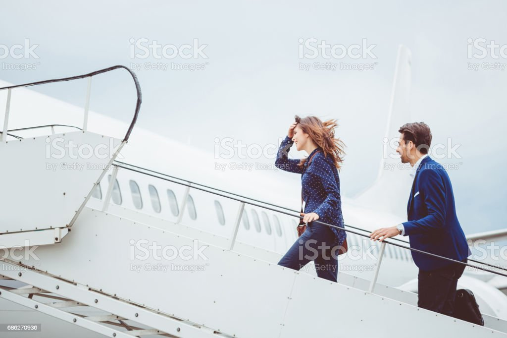 Two business people boarding airplane stock photo