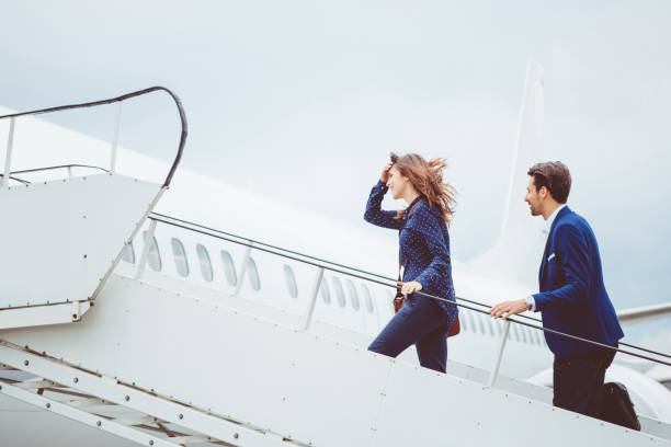two business people boarding airplane - getting on stock photos and pictures