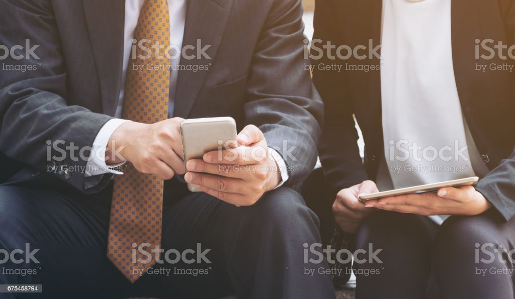 Two business people discuss business affair on mobile phone Two business people discuss business affair on mobile phone. Communication technology and business concept. Adult Stock Photo