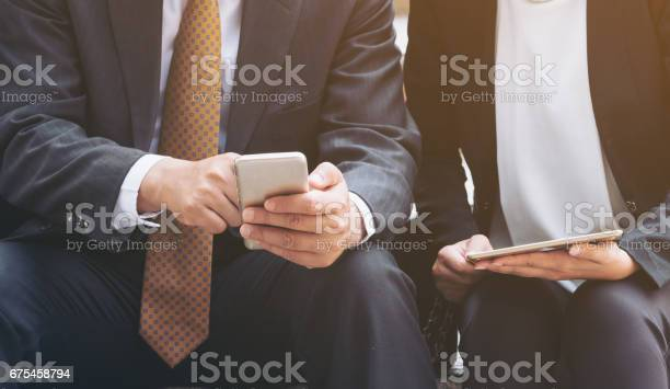 Two Business People Discuss Business Affair On Mobile Phone Stock Photo - Download Image Now