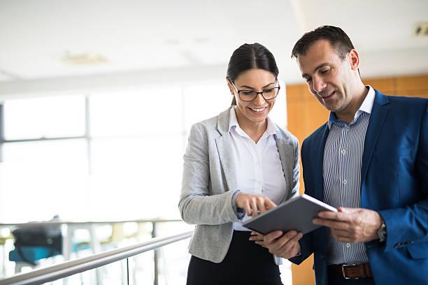 dwie osoby biznesowe omawiające strategię biznesową za pomocą tabletu cyfrowego - dwie osoby zdjęcia i obrazy z banku zdjęć