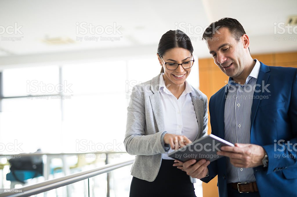 Two business people discussing business strategy using digital tablet stock photo