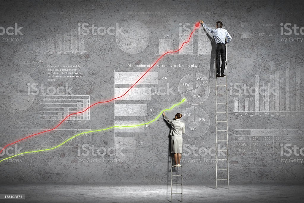 Two business people drawing climbing arrow diagram on a wall stock photo