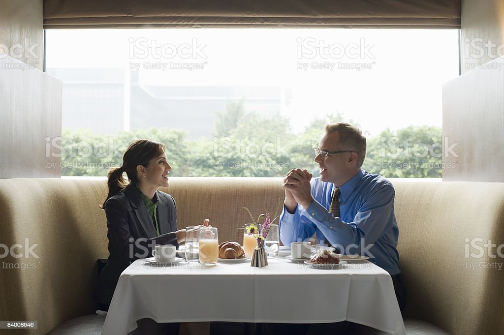 Two business people eat breakfast in restaurant. royaltyfri bildbanksbilder