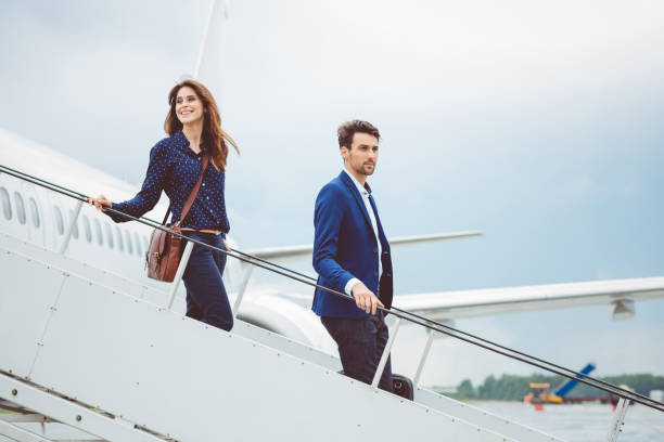 Two business people getting out of airplane stock photo
