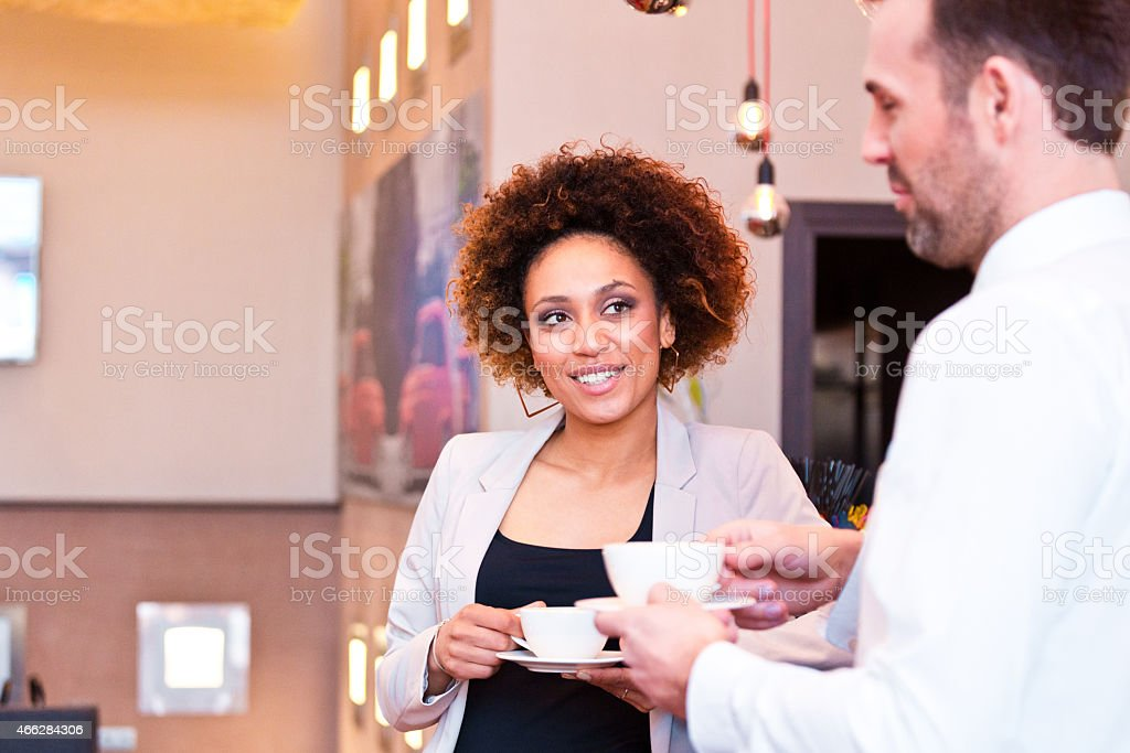 Two business people having coffee break Cheerful businessman and businesswoman talking over coffee in the bar. Focus on afro american woman. 2015 Stock Photo