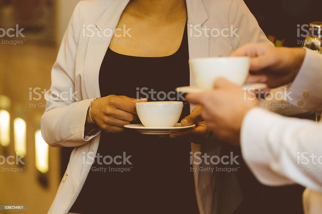 Two business people having coffee break Businessman and businesswoman talking over coffee in the bar. Close up of hands and coffee cups. Unrecognizable person. 2015 Stock Photo