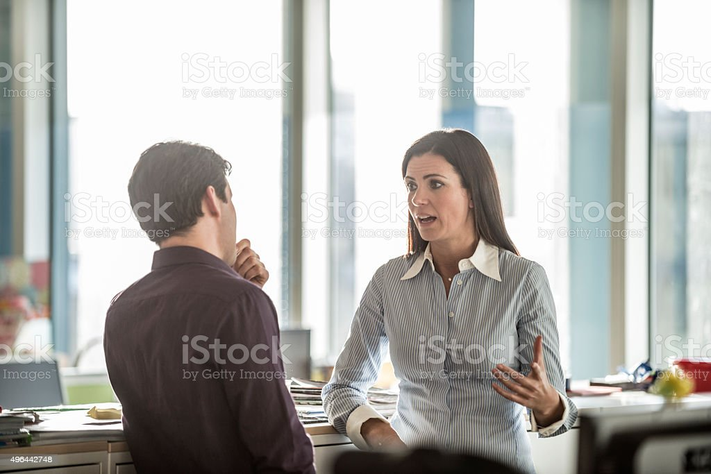 Two business people having serious discussion in modern office stock photo