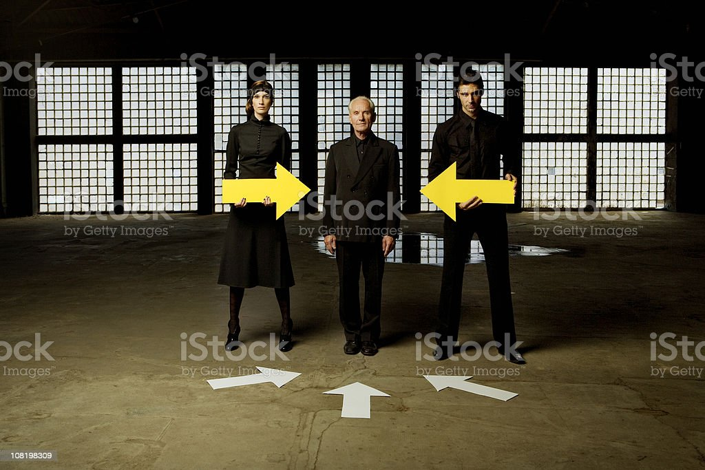 Two Business People Holding Arrows Pointed to Man royalty-free stock photo