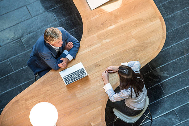 Two business people in meeting at curved desk overhead view Businessman and woman seen from above, sitting at modern shaped desk. Business people sitting in a meeting with laptop computer. Smart professional colleagues in discussion. face to face stock pictures, royalty-free photos & images