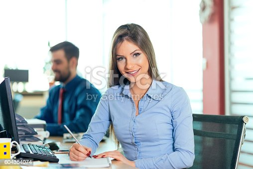 istock Two business people in office, young businesswoman and young businessman 604354074