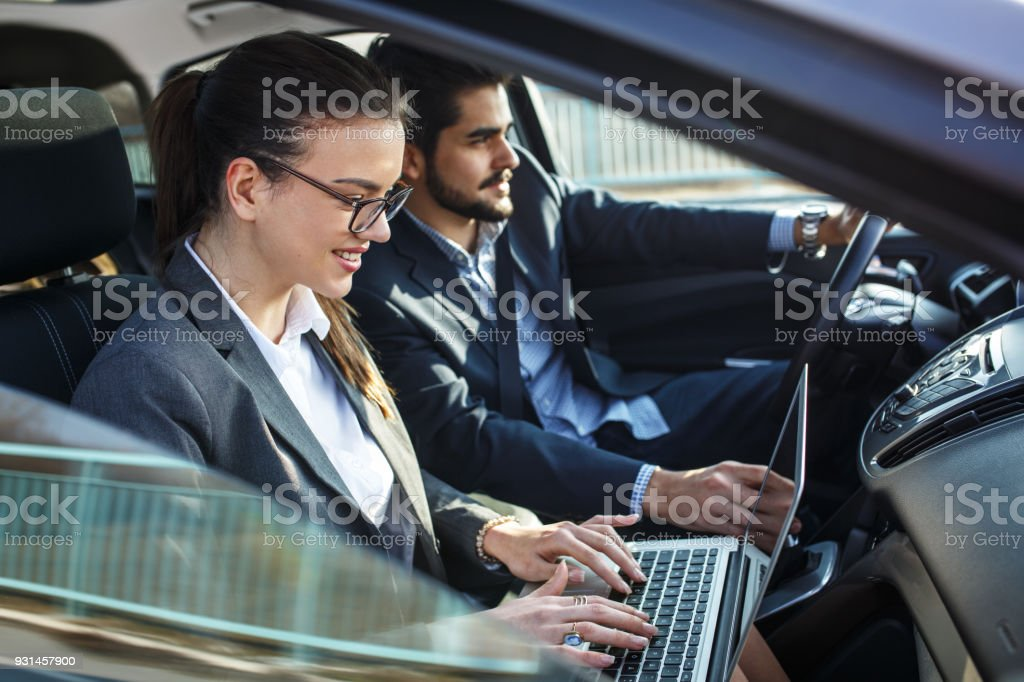 Two business people in the car.They travel to business meeting.Man...