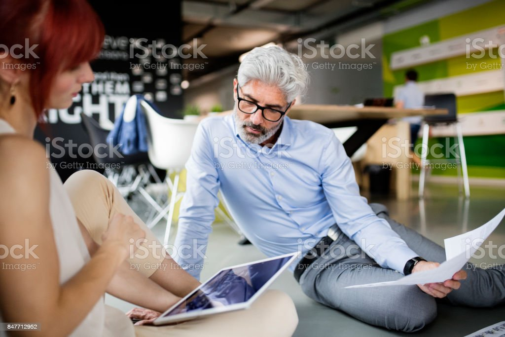 Two business people with tablet in the workplace. Woman and man...