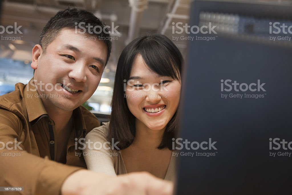 Two Business People Looking at Computer in the Office royalty-free stock photo