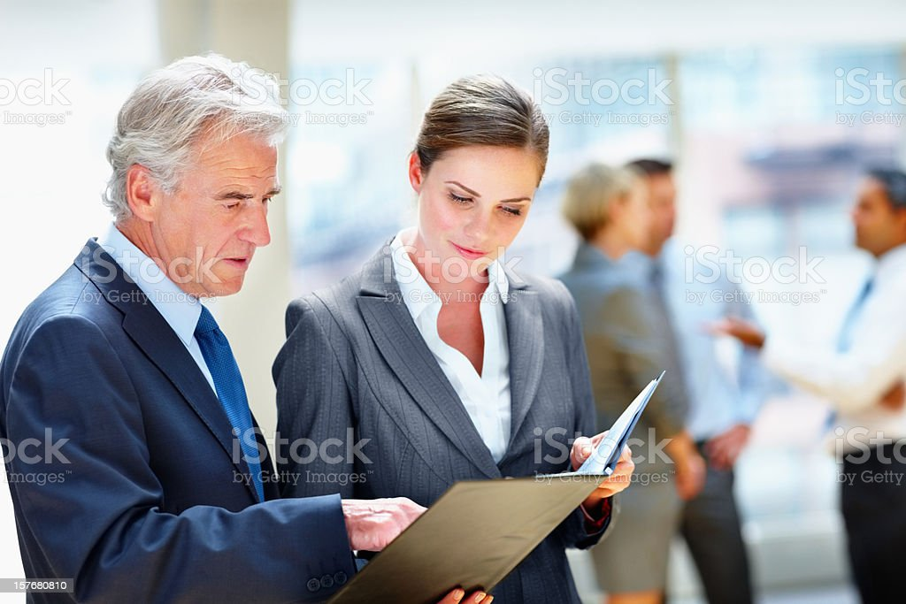Two business people looking at folder team in the background royalty-free stock photo