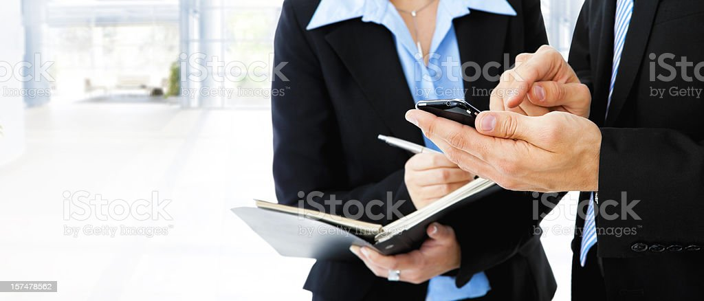 Two business people making an appointment in book and phone stock photo