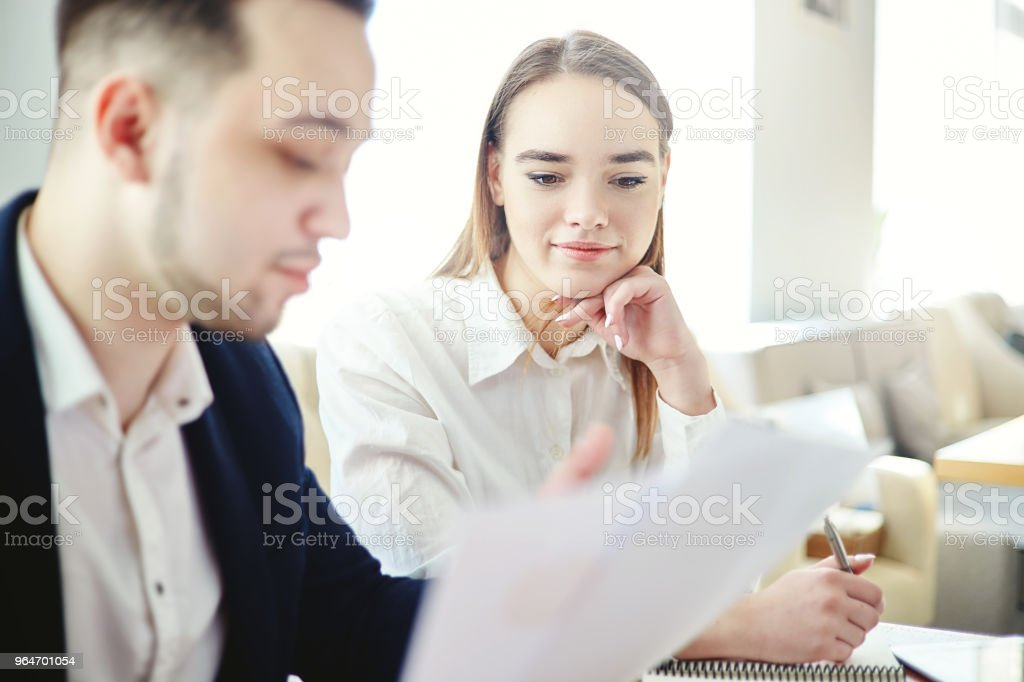 Two business people, man and woman, examining agreement at meeting. Focus on young businesswoman cooperating with male colleague royalty-free stock photo