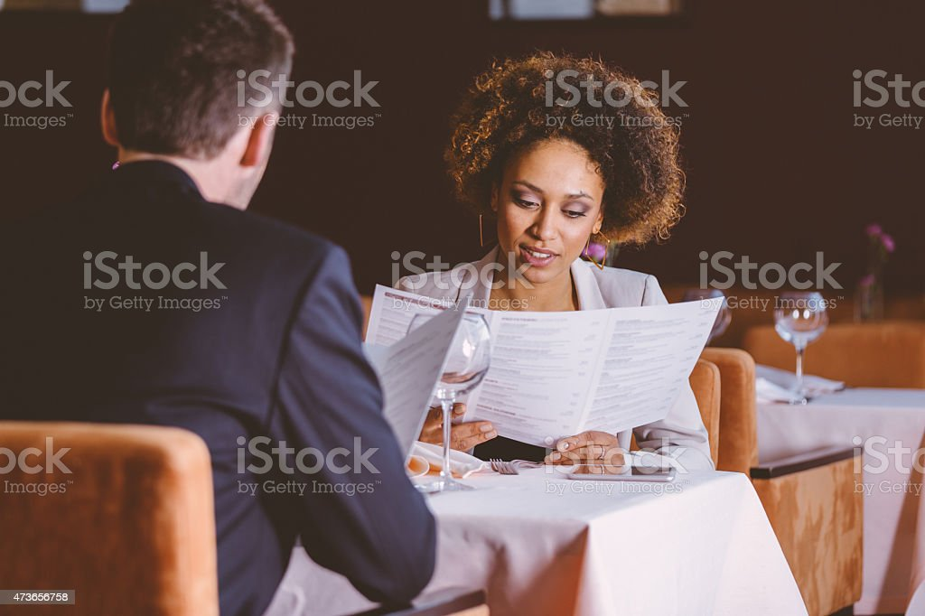 Two business people on lunch in the restaurant An afro american businesswoman and caucasian businessman having business lunch in restaurant, reading menu. 2015 Stock Photo