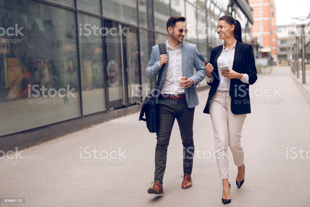 Two business people on their way to work stock photo