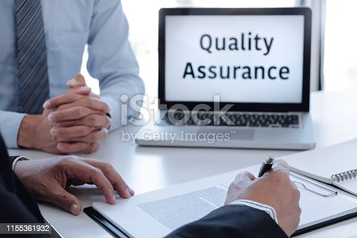 istock Two business people or insurance agent with client discussing about quality assurance. 1155361932