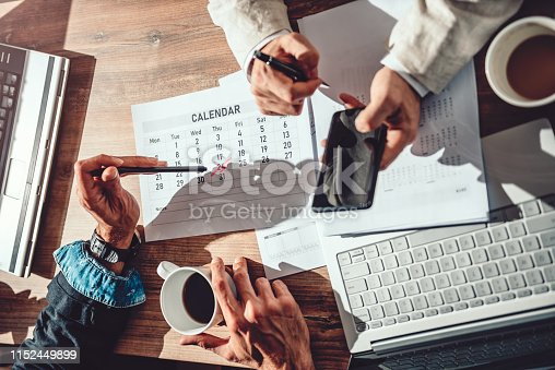 Two business people sitting at the desk and setting deadline for the next project