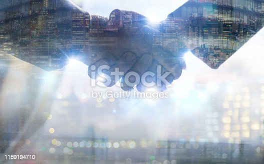 istock Two business people shaking hands as symbol of agreement, consolidation, business development and support. Multiple exposure image 1159194710