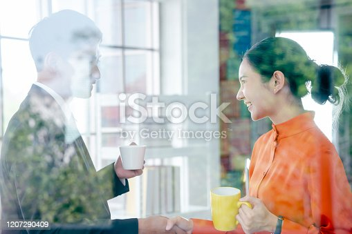 623122018 istock photo Two business people shaking hands on coffee break, view through window 1207290409